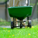 Man Pushing Spreader with Herbicides Across Lawn