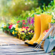 Colorful flower bed with yellow gardening boots, Features various lawn & garden tools.