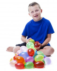 Boy with a pile of water balloons isolated on white background